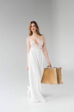 Stylish girl holding suitcase while walking on grey stock vector