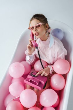 overhead view of young woman in sunglasses talking on retro phone while lying in bathtub with pink air balloons on white