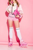 cropped view of stylish girl talking on retro phone while standing in roller-skates on pink