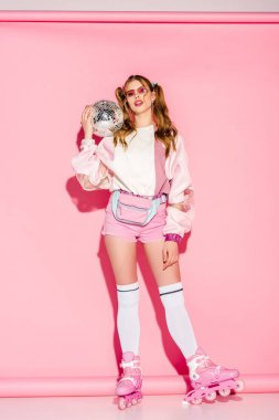 attractive girl in sunglasses holding disco ball while standing in roller-skates on pink