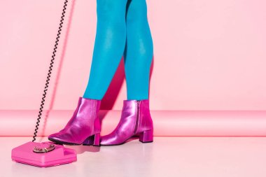 cropped view of young woman in blue tights near retro phone on pink