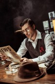 Concentrated detective in glasses reading newspaper in dark office