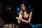 Fotografie Beautiful woman with mouthpiece lighting cigarette with lighter in dark office