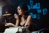 schöne Frau mit Mundstück zündet Zigarette mit Feuerzeug im dunklen Büro an