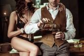 Teilbild einer sexy Frau in schwarzen Dessous, die auf einem Holztisch sitzt und mit einem Detektiv im Büro flirtet