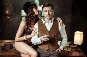 Fotografie sexy Frau in schwarzen Dessous sitzt auf Holztisch und flirtet mit Detektiv im Büro