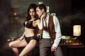 Sexy Frau in schwarzer Dessous sitzt auf Holztisch und flirtet mit Detektiv im Büro