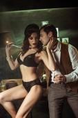 sexy Frau in schwarzen Dessous sitzt auf Holztisch und flirtet mit Detektiv im Büro