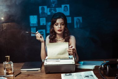 Pensive woman with mouthpiece using typewriter in dark office