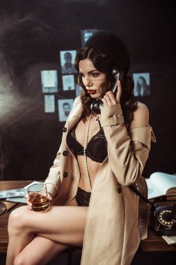 Sexy woman in black lingerie and trench coat holding glass of cognac while talking on telephone stock vector
