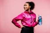 beautiful smiling african american sportswoman with sport bottle isolated on pink
