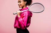 krásné usměvavé africká americká sportovkyně držící tenisovou raketu izolované na růžová