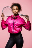 Photo beautiful african american sportswoman with tennis racket posing and looking at camera isolated on pink