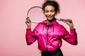 Photo beautiful african american sportswoman holding tennis racket, looking at camera and smiling isolated on pink