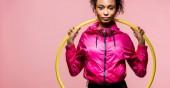 Panoramaaufnahme der schönen afrikanisch-amerikanischen Sportlerin mit Hula-Hoop-Reifen, die isoliert auf rosa Kamera schaut