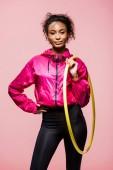 schöne afrikanisch-amerikanische Sportlerin blickt in die Kamera und hält Hula-Hoop-Reifen isoliert auf rosa