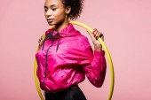 attraktive afrikanisch-amerikanische Sportlerin posiert mit Hula-Hoop-Reifen auf rosa