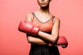 cropped view of african american sportswoman in boxing gloves posing isolated on coral