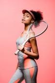 atraktivní africká americká sportovkyně v sluneční clona držící tenisovou raketu a při pohledu na fotoaparát izolované na coral