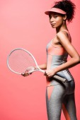 beautiful african american sportswoman in sun visor holding tennis racket and looking at camera isolated on coral