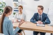Rückansicht einer Frau, die während des Bewerbungsgesprächs mit Personalvermittlern spricht