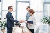 Glückliche Mitarbeiterin schüttelt die Hände mit Rekrutierer im Vorstellungsgespräch