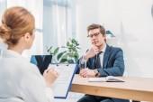 Fotografia uomo pensoso in bicchieri seduti vicino reclutatore con appunti sul colloquio di lavoro