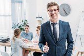 Selektiver Fokus des gut gelaunten Recruiters in Brille, die den Daumen in der Nähe von Mitarbeitern zeigt