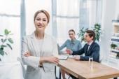 Fotografia focus selettivo di donna allegra in piedi con le braccia incrociate vicino ai colleghi