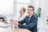 Fotografie gutaussehender Personalvermittler mit Brille lächelt neben attraktivem Mitarbeiter