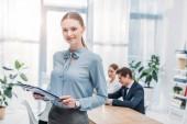 selektivní zaměření veselé ženy stojící se schránkou u spolupracovníků