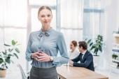 Fotografia donna allegra in piedi con le mani strette vicino ai colleghi in ufficio
