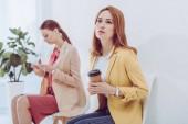 Nachdenklicher Angestellter mit Pappbecher nahe Frau mit Smartphone im Fokus