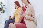 Ausgeschnittene Ansicht einer nachdenklichen Frau mit Smartphone in der Nähe von Angestellten mit Pappbecher