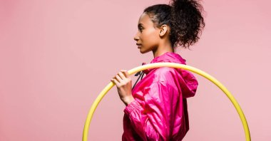 panoramic shot of beautiful african american sportswoman posing with hula hoop isolated on pink with copy space