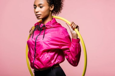 attractive african american sportswoman posing with hula hoop isolated on pink