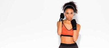 panoramic shot of athletic african american sportswoman in sport gloves looking at camera on white