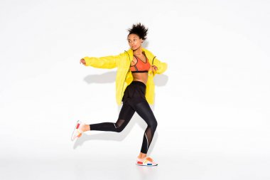 athletic african american sportswoman in yellow sports jacket running on white