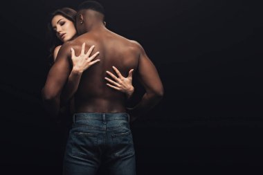 Back view of beautiful sexy woman hugging shirtless african american man isolated on black stock vector