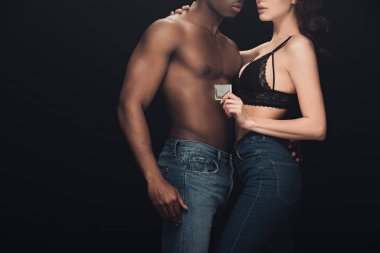Cropped view of sexy woman embracing shirtless african american man and holding condom isolated on black stock vector