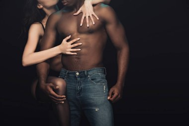 Partial view of sexy woman passionately hugging shirtless african american man isolated on black stock vector