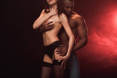 shirtless african american man embracing topless woman on dark with red light