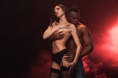 african american man embracing beautiful topless woman on dark with red light and copy space