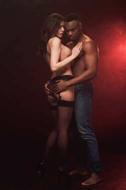 african american man embracing beautiful topless woman on dark with red light