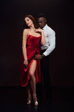 Beautiful seductive interracial couple in formal wear posing isolated on black stock vector