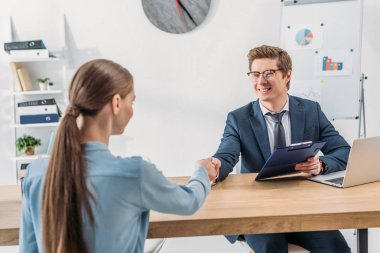 woman shaking hands with cheerful recruiter in glasses holding clipboard