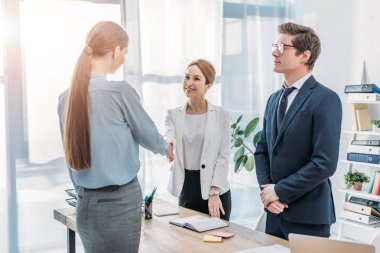 cheerful recruiter standing near colleague in glasses and shaking hands with woman