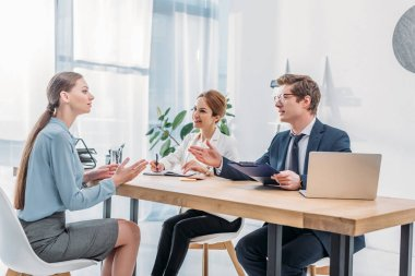 attractive woman speaking with recruiters during job interview