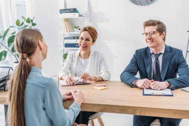 back view of employee speaking with cheerful recruiters during job interview