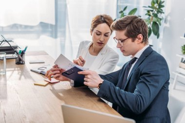 Attractive hr looking at clipboard near coworker in glasses while sitting in office stock vector